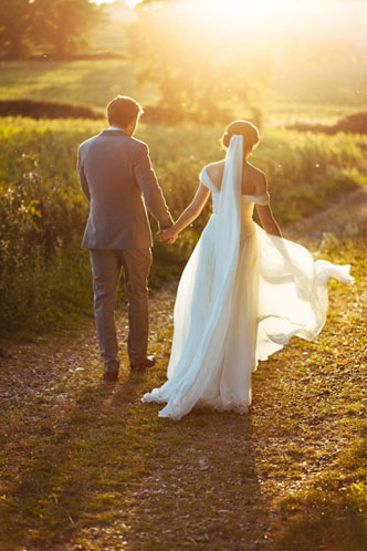 bride and groom walking in sunset